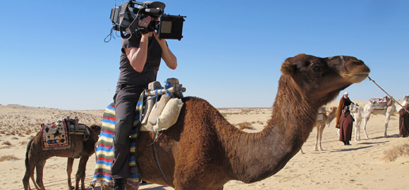 Cameraman riding a camel