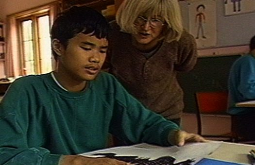 Boy reading with teacher